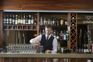 A bartender behind the bar pouring cocktails