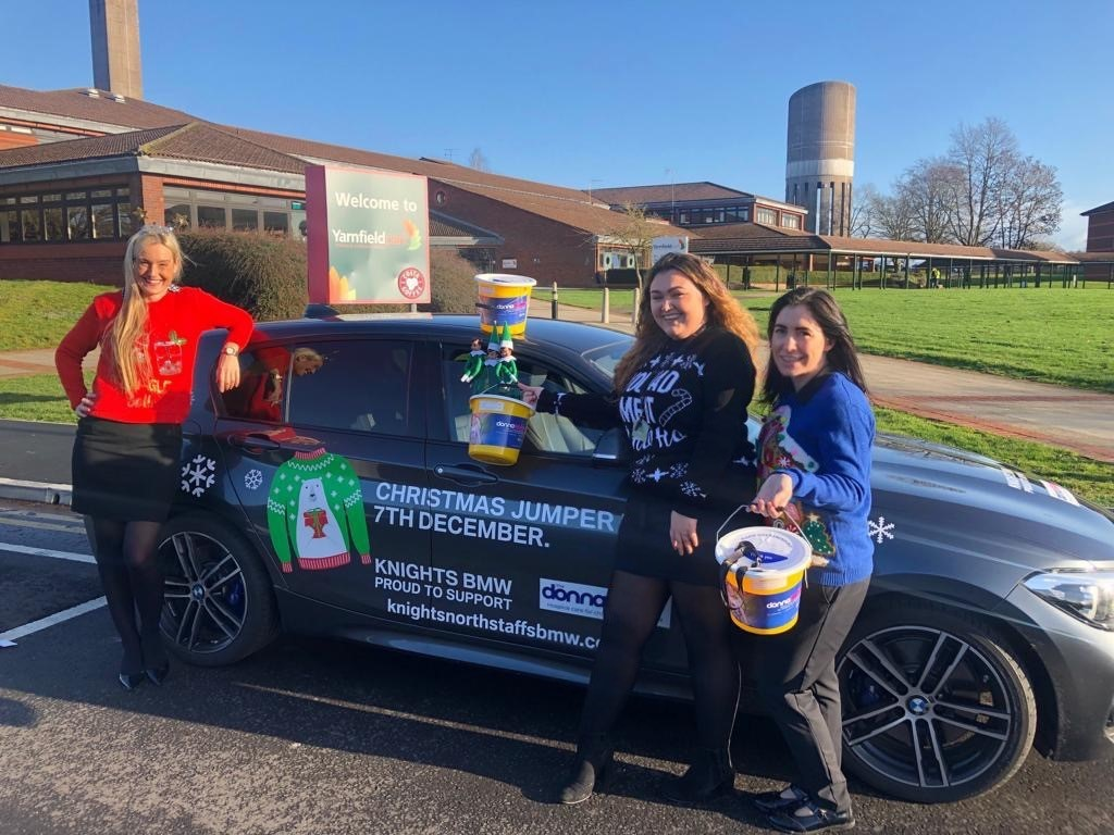 Workers in front of a car raising money