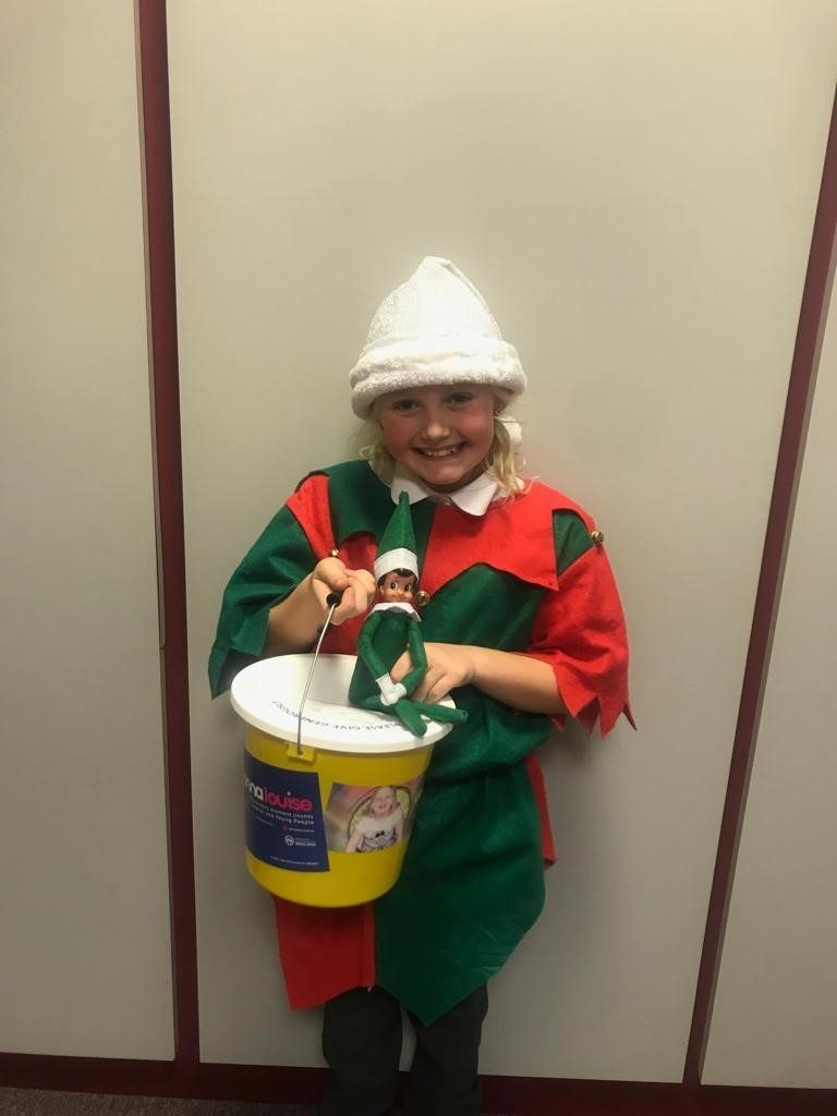 A women holding a charity bucket dressed in a festive outfit